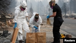 Forensic anthropologists Kyra Stull and Tatiana Vlemincq work with San Mateo County Deputy Coroner Elizabeth Ortiz to recover human remains from a trailer home destroyed by the Camp Fire in Paradise, California, U.S., November 17, 2018.