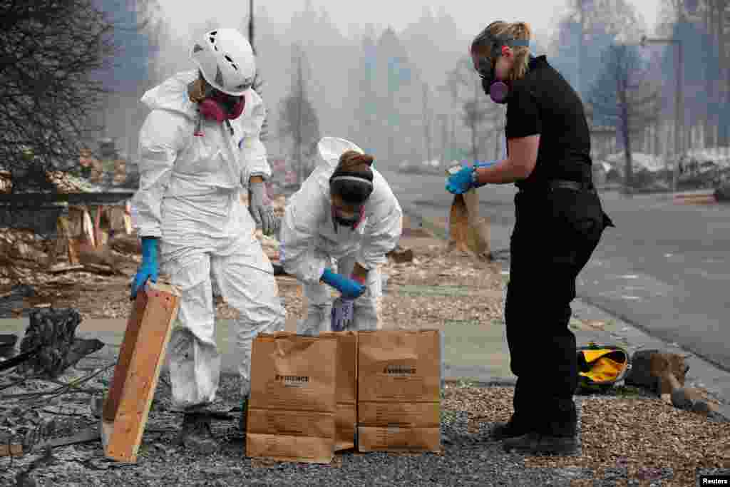 (L-R) Forensic anthropologists Kyra Stull and Tatiana Vlemincq work with San Mateo County Deputy Coroner Elizabeth Ortiz to recover human remains from a trailer home destroyed by the Camp Fire in Paradise, California, Nov. 17, 2018.