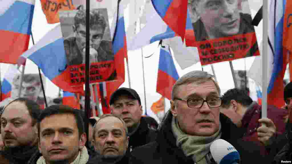Opposition leader and Russia's former Prime Minister Mikhail Kasyanov, right, speaks to the media with opposition activist Ilya Yashin, left, during a march to commemorate Kremlin critic Boris Nemtsov, who was shot dead Friday, in Moscow, March 1, 2015.