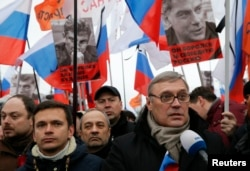 FILE - Opposition leader and Russia's former Prime Minister Mikhail Kasyanov, right, speaks to the media with opposition activist Ilya Yashin, left, during a march to commemorate Kremlin critic Boris Nemtsov, who was shot dead, in Moscow, March 1, 2015.