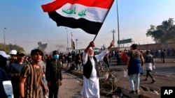 A protester waves the national flag during clashes with security forces in central Baghdad, Iraq, Monday, Jan. 20, 2020. Iraqi security forces also used live rounds, wounding over a dozen protesters, medical and security officials said, in…