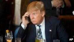 FILE - Donald Trump saat menjadi kandidat presiden dari partai Republik menggunakan telepon seluler saat istirahat makan siang North Charleston, S.C., 18 Februari 2016. Presiden Trump melalui Twitter pada 29 Juli 2017 mengkritik para senator. (Foto:Dok)
