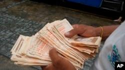 Un hombre cuenta billetes por el equivalente a un dólar en una parada de autobús en Caracas, el 5 de agosto de 2021.