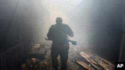 Một phần tử nổi dậy thân Nga đi trong khu chợ bị nã pháo ở quận Petrovskiy, thị trấn Donetsk, miền đông Ukraine, 26/8/2014.