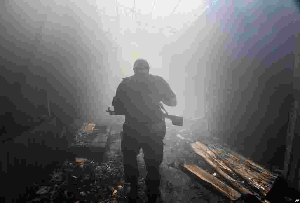 A pro-Russian rebel walks in a passage at the local market damaged by shelling in the Petrovskiy district, town of Donetsk, eastern Ukraine, Aug. 26, 2014.