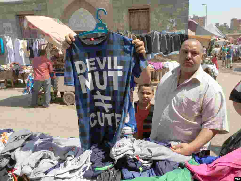 """Khaled El-Antably and with his sons Ahmed and Mahmoud are buying new shirts for the hot summer. Khaled says """"Prices here is very low compared to the big malls. The quality is not the best, but what can we do? Nothing lasts."""" 27 May 2016, Cairo. (Photo"""