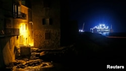 The Costa Concordia (R) cruise liner is seen at Giglio harbor at Giglio Island, early July 18, 2014.