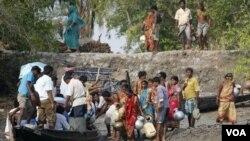 Penduduk desa di Bangadesh menerima bantuan air bersih dari sebuah organisasi non-pemerintah setelah sebuah kapal alami kecelakaan.