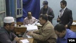 Para petugas di Kairo, Mesir melakukan perhitungan atas referendum hari Minggu (20/3).