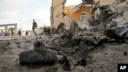 A Somali soldier observes the scene of a car bomb attack in the capital Mogadishu, Somalia, June 21, 2015.