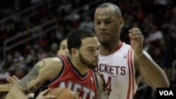 Deron Williams, kiri, berusaha melewati pemain Houston Rockets Chuck Hayes dalam pertandingan hari Sabtu (26/2) di Houston. Akhir pekan ini New Jersey Nets akan menghadapi Toronto Raptors di London.