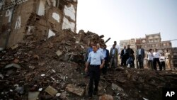 Peter Maurer, the president of the International Committee of the Red Cross, center, walks near houses destroyed by a Saudi-led airstrike during his visit to the old city of Sana'a, Yemen, Aug. 9, 2015.