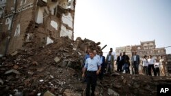 FILE - Peter Maurer, the president of the International Committee of the Red Cross, center, walks near houses destroyed by a Saudi-led airstrike during his visit to the old city of Sanaa, Yemen, Sunday, Aug. 9, 2015.
