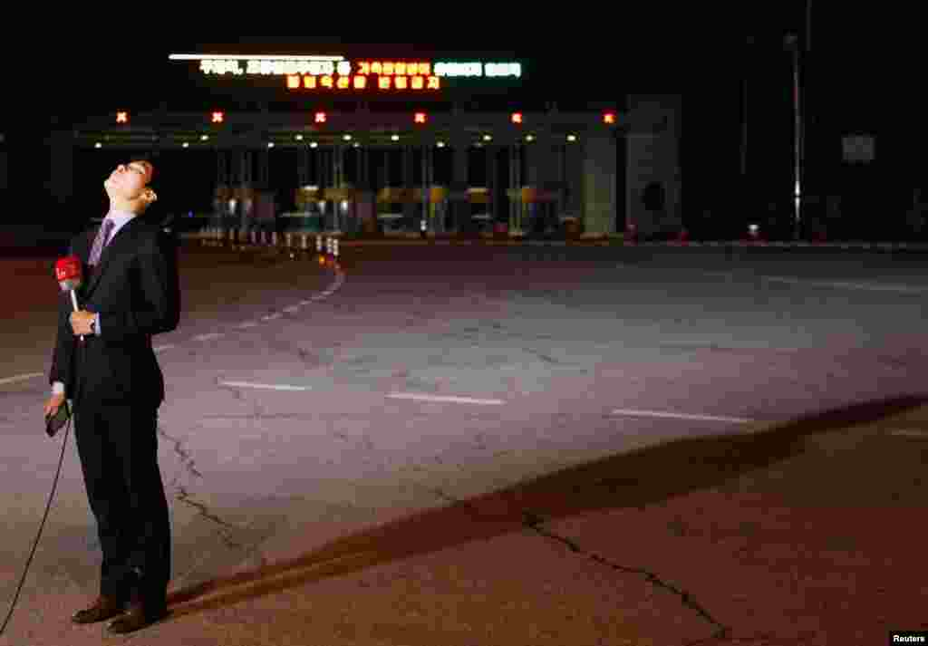 A TV reporter prepares for a news report in front of an empty gate at the customs, immigration and quarantine (CIQ) office in Paju, South Korea, April 29, 2013.