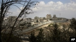 A general view shows the Palestinian Shuafat refugee camp behind Israel's controversial separation barrier in east Jerusalem, 09 Oct 2010