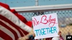 ٹیکساس میں اس مقام پر ہونے والے ایک مظاہرے میں شریک شخص نے ایک کتبہ اٹھا رکھا ہے جہاں والدین سے الگ کیے جانے والے تارکِ وطن بچوں کو رکھا گیا ہے۔