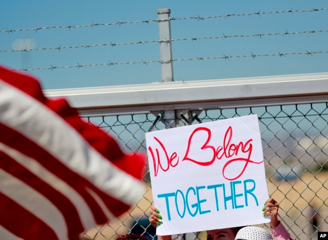 FILE - A protester holds a sign outside a closed gate at the Port of Entry facility, June 21, 2018, in Fabens, Texas, where tent shelters are being used to house separated family members.