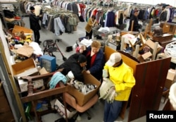 FILE - People look for clothes at the Capuchin Soup Kitchen service center in Detroit, where hundreds of people receive food and supplies every day.