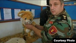 A Kurdish fighter holds a stuffed teddy bear, used to conceal a weapon. It's just one item gathered from battles against Islamic State militants and to be displayed as part of a museum in Duhok, Iraq. (VOA/Kawa Omar)
