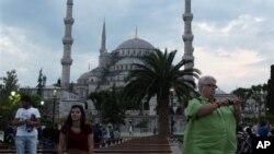Des touristes prennent des photographies en face de la Mosquée bleue à Istanbul, Turquie, le 4 juin 2013.