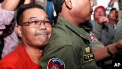 Hong Sok Hour, left, a senator from the opposition Cambodia National Rescue Party, is escorted by riot police officers, center, at Phnom Penh Municipal Court in Phnom Penh, Cambodia, Oct. 2, 2015.