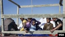 Anak-anak Libya duduk di bagian belakang sebuah truk untuk berlindung, saat baku tembak antara pasukan Gaddafi dan pemberontak di Brega (17/6).