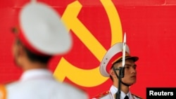 Binh lính quân đội đứng bảo vệ trước biểu tượng của Đảng Cộng sản Việt Nam trong buổi lễ kỷ niệm 85 năm thành lập Đảng tại Hà Nội ngày 2/2/2015.