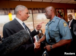 Attorney General Eric Holder talks with Capt. Ron Johnson of the Missouri State Highway Patrol at Drake's Place Restaurant in Ferguson, Missouri, August 20, 2014.