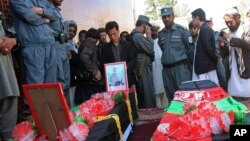 Afghan men stand over the coffins of two police officers killed in a roadside bombing in Ghazni province on April 28, 2013.