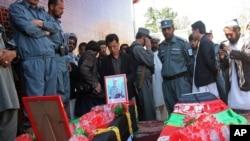 4月28日阿富汗人站在两名加兹尼省被路边炸弹杀害的两名警方人员的灵柩旁