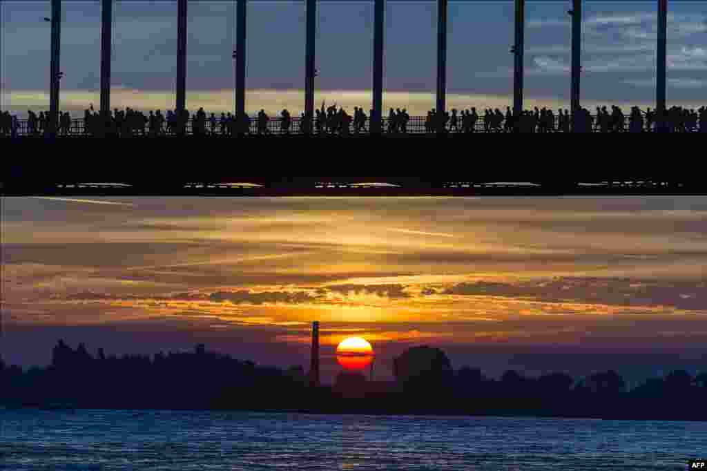 "Walkers cross the Waalbrug River during sunrise on the first day of the 98th annual four-day walking event ""The Vierdaagse"" in Nijmegen, The Netherlands."