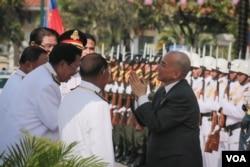 ព្រះមហាក្សត្រ ព្រះបាទ នរោត្តម សីហមុនី យាងនិវត្តន៍ពីអង្គពិធី ក្រោមគារវកិច្ចរបស់លោកនាយករដ្ឋមន្ត្រី ហ៊ុន សែន និងមន្ត្រីជាន់ខ្ពស់ដទៃទៀត។ (អូន ឆេងប៉រ /VOA Khmer)