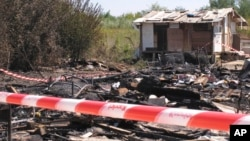 FILE - A Gypsy camp on the outskirts of Rome lies in ruins after a fire, possibly caused by a candle, Aug. 27, 2010.