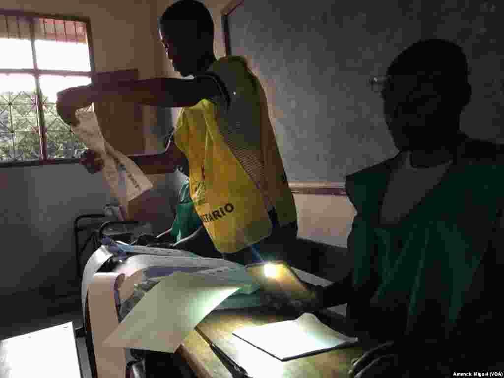 Funcionários de assembleia de voto usam lanterna de telefone para confirmar dados em boletim de voto. Wimby, Cabo Delgado, Moçambique. 15 Outubro 2019