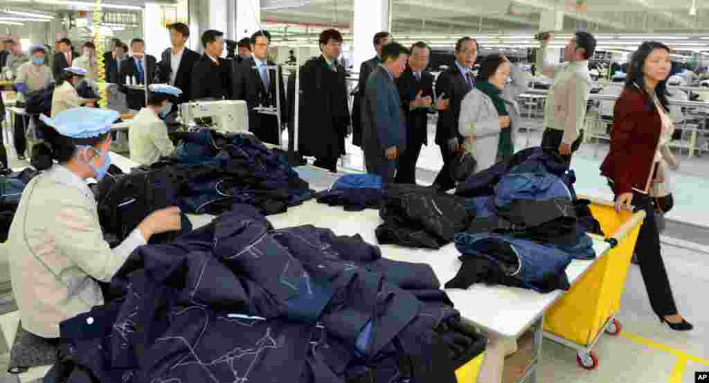 South Korean lawmakers walk past North Korean workers at a factory in the inter-Korean industrial park in Kaesong, North Korea, Oct. 30, 2013.