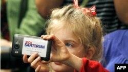 Луизиана: девочка снимает выступление Рика Санторума телефоном, на который наклеен рекламный плакатик Санторума.