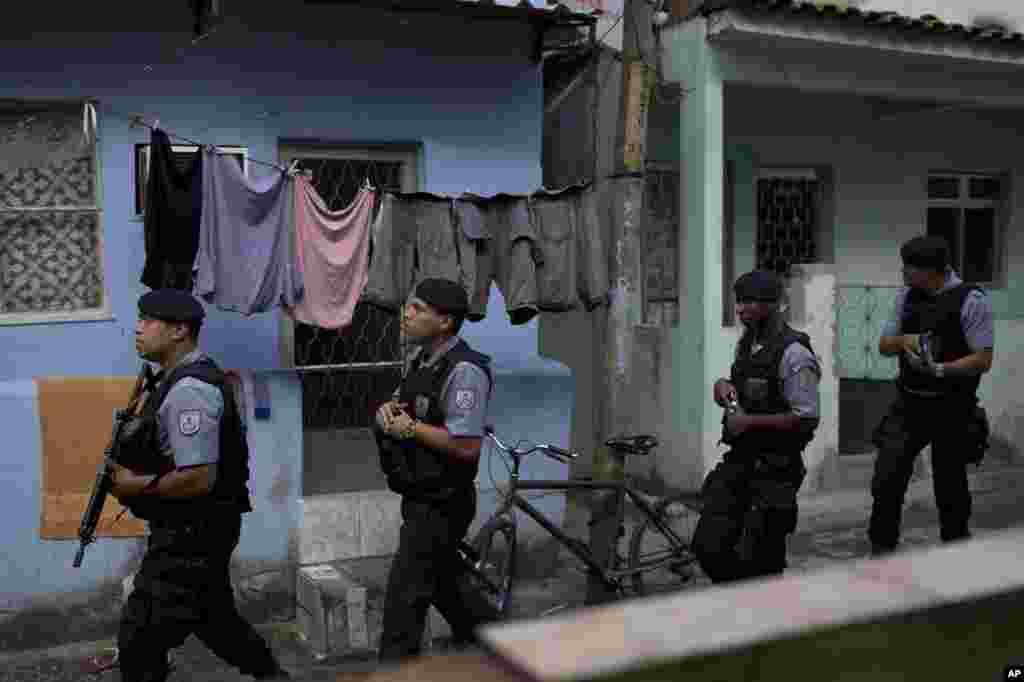 Policías de la Unidad de Pacificación (UPP) patrulla el área de Varginha en el complejo de la favela Manguinhos como parte de la seguridad por la visita del Papa.
