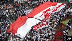 Warga Indonesia mengibarkan bendera nasional merah putih besar dan yang lebih kecil saat unjuk rasa di Jakarta, Indonesia, Minggu, 4 Desember 2016. (Foto: AP)