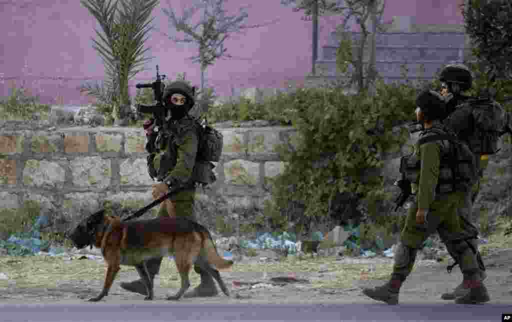 Israeli soldiers walk during an operation in the Balata refugee camp in the West Bank city of Nablus, June 17, 2014.