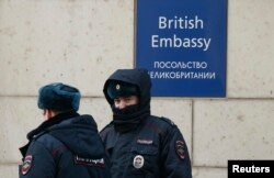 Russian policemen walk outside the British embassy in Moscow, Russia, March 17, 2018.