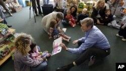 Dalam foto tertanggal 7/10/2010 ini seorang kandidat gubernur sebuah negara bagian di AS membacakan cerita kepada anak-anak. Laporan terbaru AP mendapati pejabat AS telah gagal melindungi anak yang terlantar.