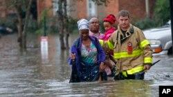 Một nhân viên thuộc Sở Cứu Hỏa St. George giúp người dân lội qua vùng nước lụt do những cơn mưa lớn gây ra trong khu chung cư Chateau Wein, Baton Rouge, La., thứ 6, ngày 12 tháng 08 năm 2016. (AP/Gerald Herbert)