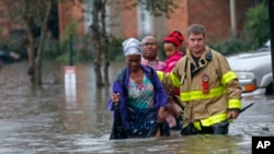 A member of the St. George Fire Department assists residents as they wade through floodwaters from heavy rains in the Chateau Wein Apartments in Baton Rouge, La., Friday, Aug. 12, 2016.