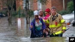 2016年8月12日巴吞鲁日市圣乔治消防局的一名消防员协助居民通过洪水。
