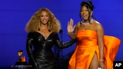 Beyonce, left, and Megan Thee Stallion accept the award for best rap song for 'Savage' at the 63rd annual Grammy Awards in Los Angeles, California, March 14, 2021. (AP Photo/Chris Pizzello)