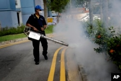 A pest control worker fumigates drains at a local housing development where Zika infections were reported in Singapore, Sept. 1, 2016.