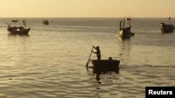Nelayan dari pulau Ly Son, provinsi Quang Ngai-Vietnam mendayung perahunya menuju kapal penangkapan ikan yang lebih besar di tengah laut (10/4). Pemerintah Tiongkok telah membebaskan 21 nelayan Vietnam yang ditangkap sebulan yang lalu dari wilayah perai