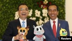 中國總理李克強和印度尼西亞總統佐科維多多在印尼總統府分享輕鬆時刻,手持2018年亞運會的吉祥物。(2018年5月7日)
