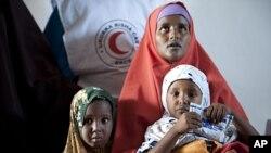 一名索马里妇女带着孩子到红十字会开设的诊所看病(资料照)