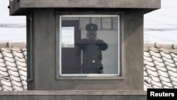 지난해 4월 북한 접경도시 신의주의 국경 초소에서 북한 병사가 망원경으로 중국 쪽을 바라보고 있다. 압록강 너머 중국 단둥에서 촬영한 사진이다. (자료사진)
